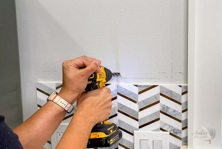 woman making hole in wall with drill bit to install toggle bolts