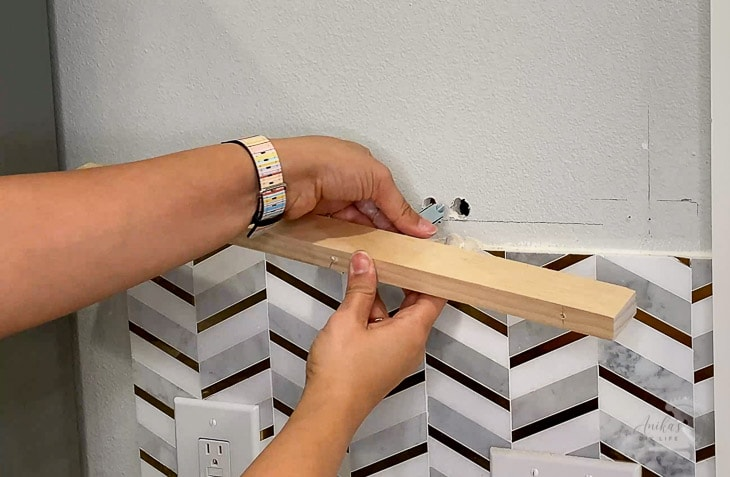 Woman inserting toggle bolt into wall to install