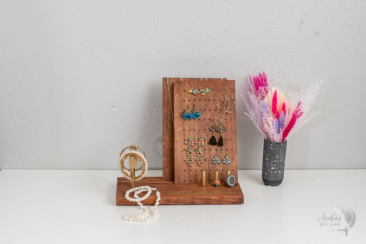 DIY jewelry holder on table with pink flowers