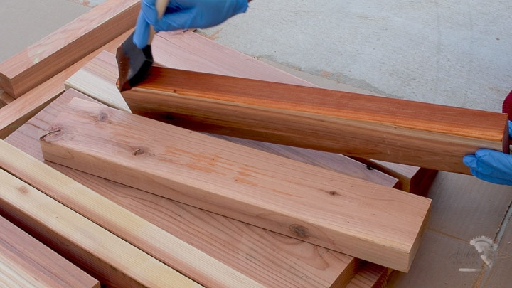 woman staining redwood boards to build a DIY outdoor box