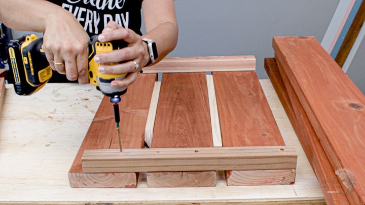 woman building the short side by attaching 2x2 rails