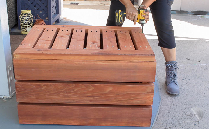 woman attaching the bottom of the DIY storage box