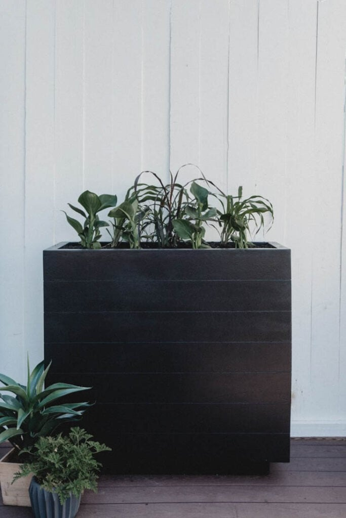 Tall wooden planter box stained dark brown