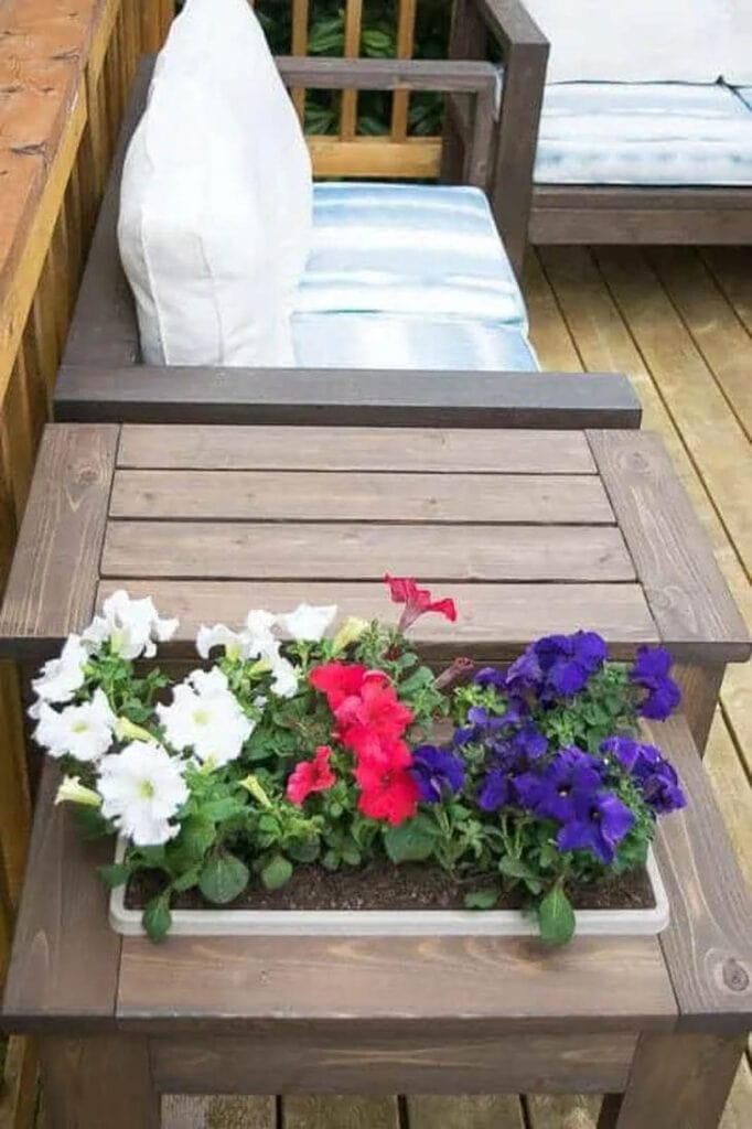 flowers in a DIY wood planter built into an outdoor end table