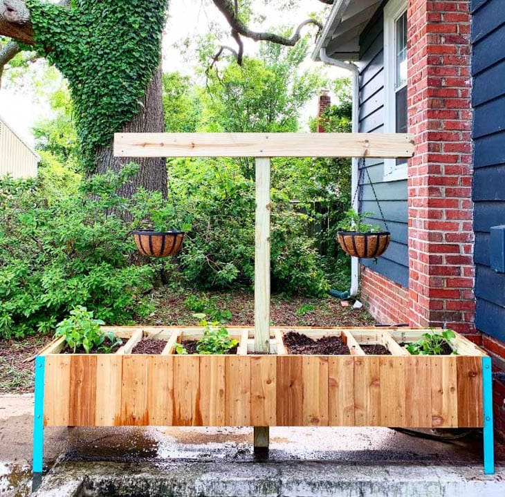 raised garden bed with t and arms to hold hanging flower pots