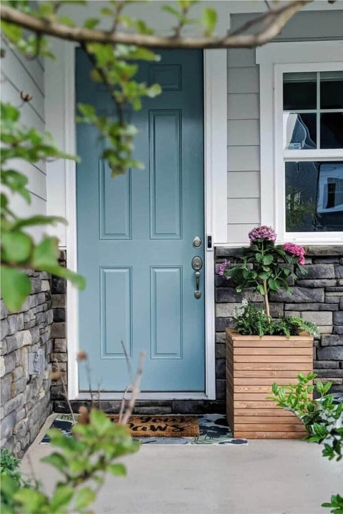 Wood planter box on front porch with blue front doof