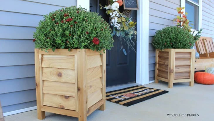 2 DIY wood planter boxes in porch with mums in them