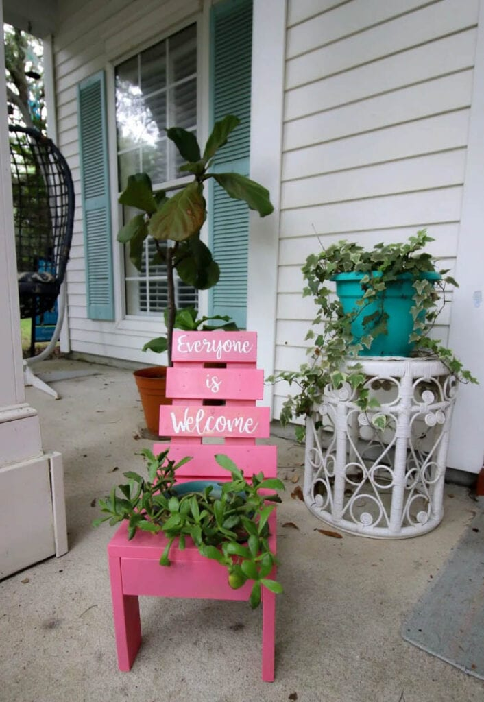pink wooden planter shaped like a chair