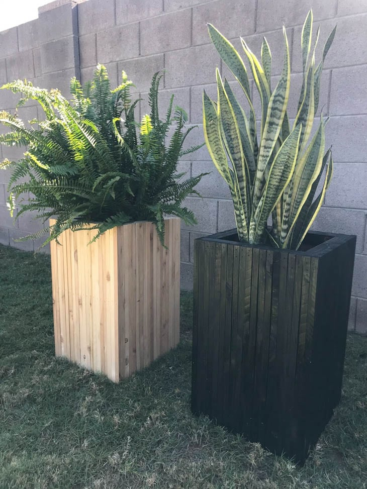 two tall wood planters made from scrap wood one stained black one natural