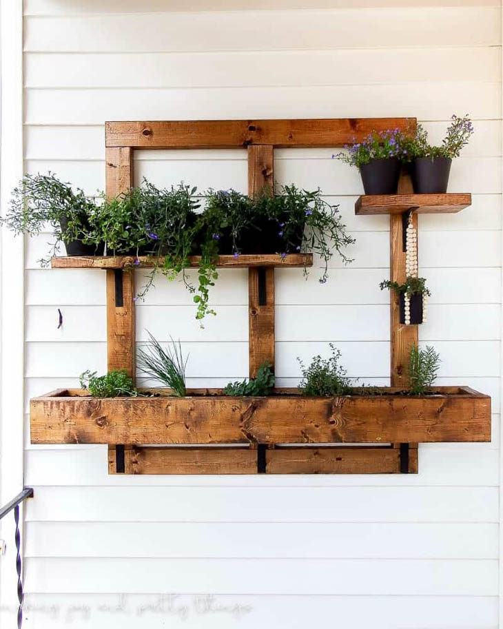 vertical wooden planter box system hanging on the outside of the house