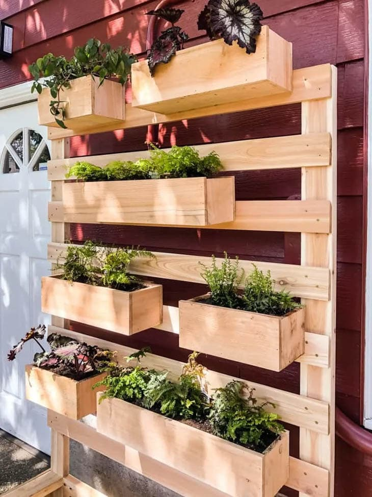 Slatted wooden wall with wood planter boxes attached