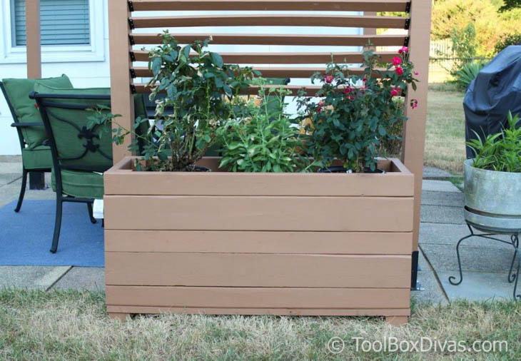 large wood planter box with greenery next to outdoor space
