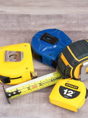 Several tape measures on a wood background