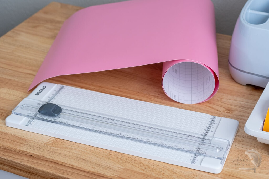 13 inch portable trimmer from Cricut on table with pink vinyl