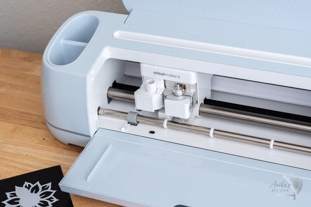 Cricut maker 3 open on a table with cut vinyl