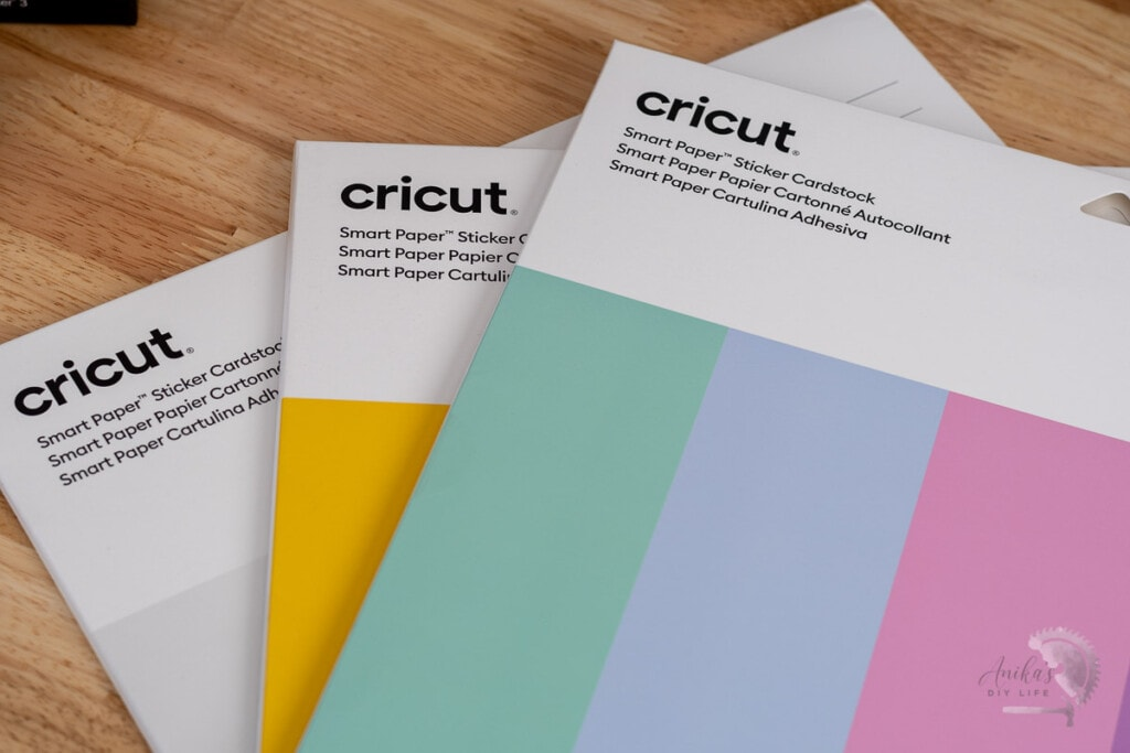 Cricut Smart Paper Sticker Cardstock on table in three colors