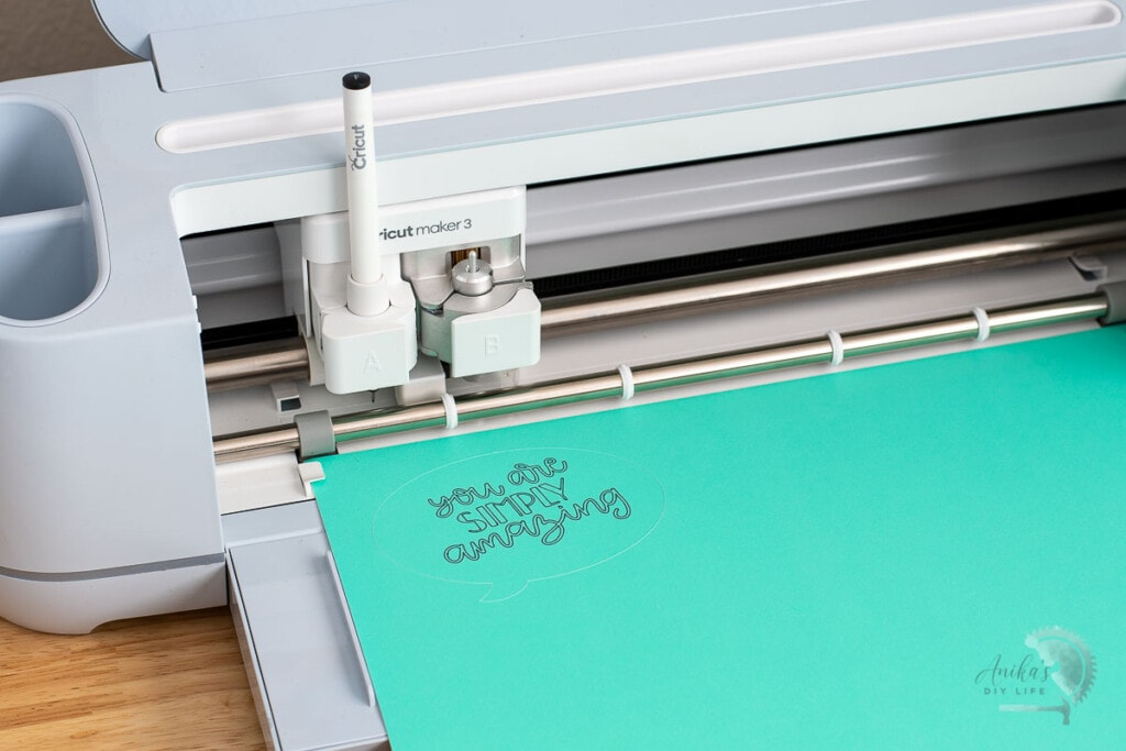 Cricut maker 3 writing and cutting a conversation bubble on teal paper