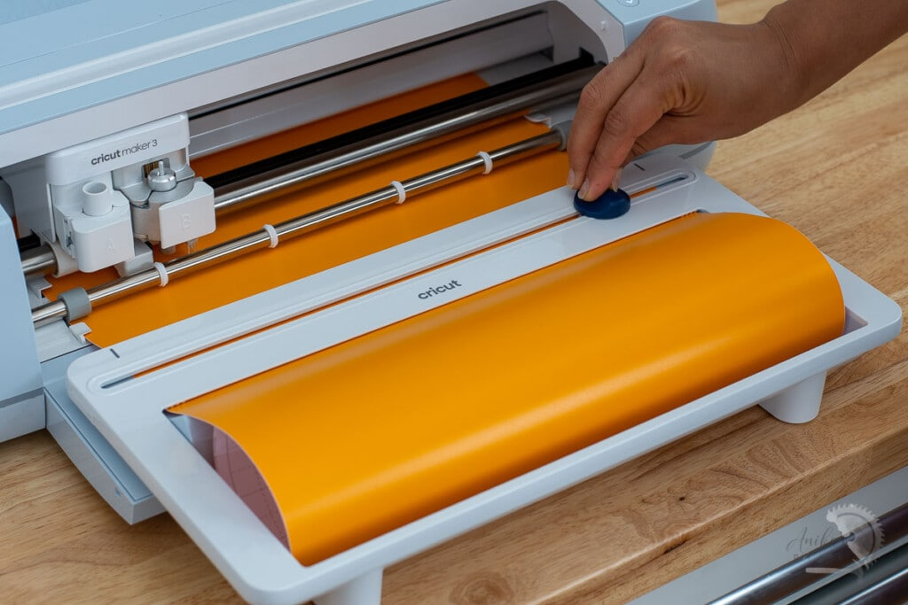 Cricut Paper holder with Orange vinyl and woman trimming off the vinyl with built in trimmer