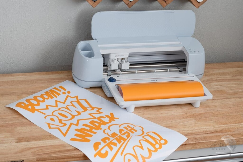 Cricut Maker 3 on Table with orangle roll and large comic book word art cut out next to it