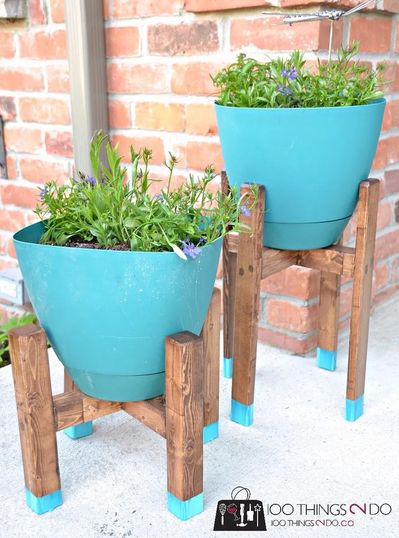 wooden four legged plant stands with teal pots