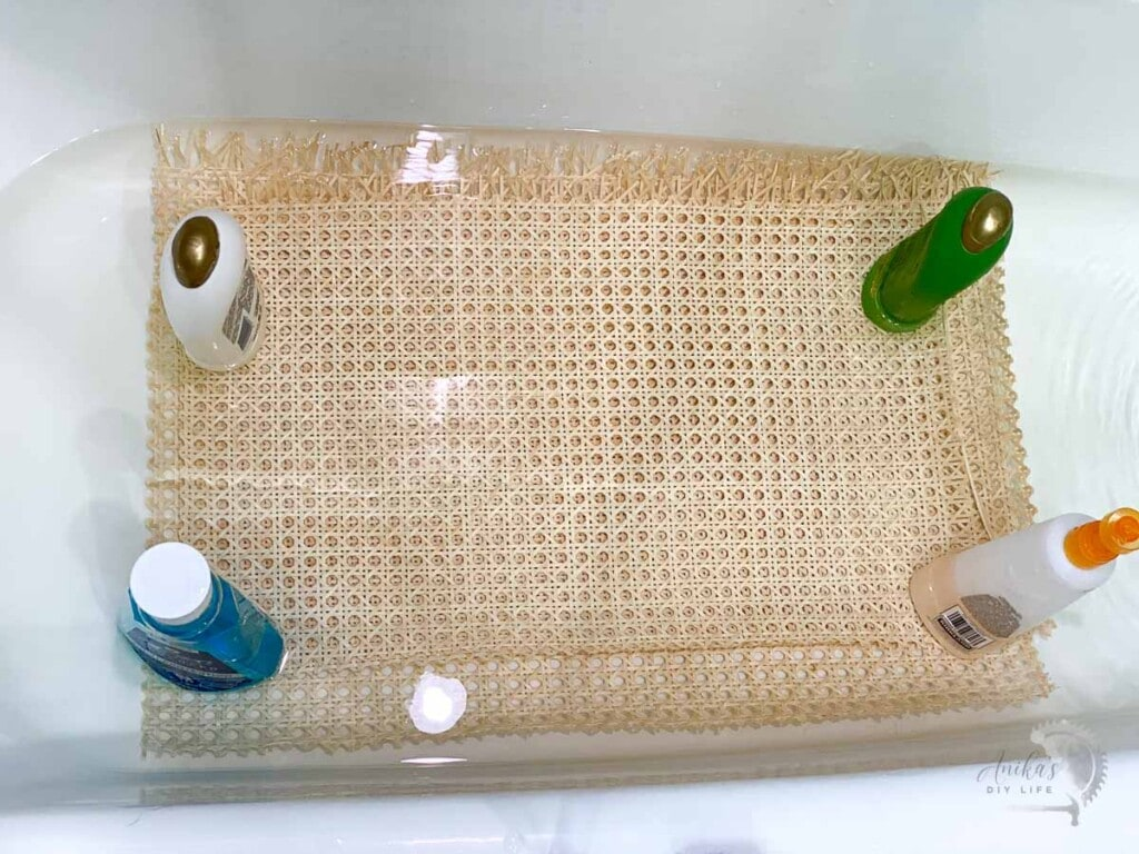 Cane webbing being soaked in hot water in bathtub and held down by bottles