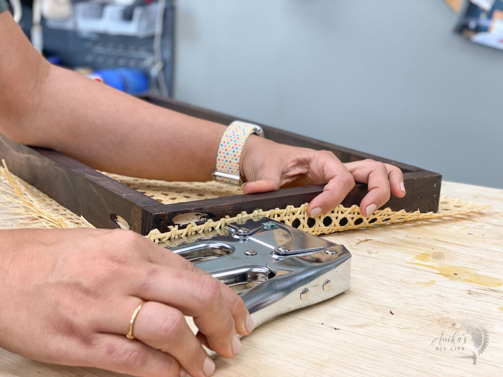 Woman attaching cane webbing to a brown wooden frame using staple gun