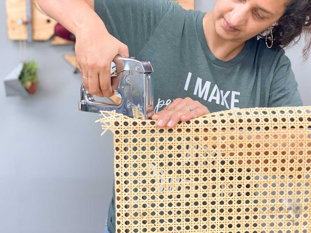 Woman attaching the second side of the cane webbing to the brown frame with a staple gun