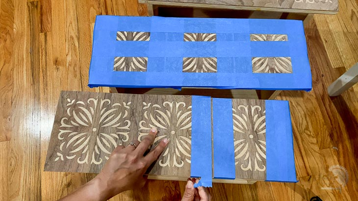 woman applying painters tape to apply veneer to drawer front.