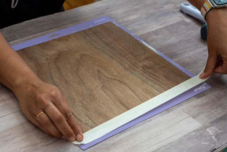 woman loading veneer onto a Cricut mat to make dresser drawer fronts