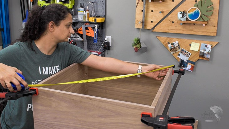 Woman measuring box for square with measuring tape