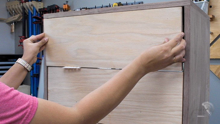 Woman installing plywood drawer fronts on a simple DIY dresser
