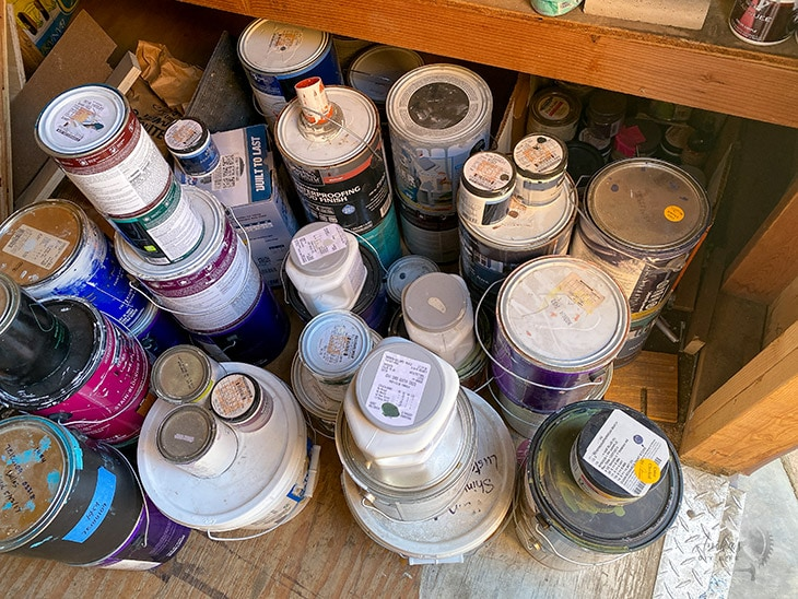 Cans of paint cluttered on floor