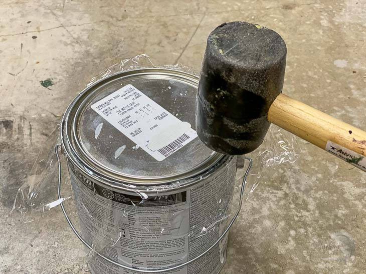 Tapping the paint can closed with a mallet