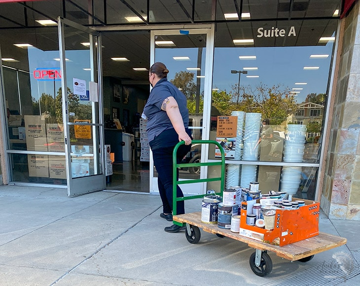 woman rolling away paint in a cart for recycling