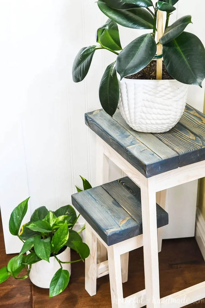 two DIY plant stands with dark painted tops