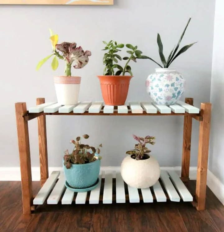 two shelf slated plant stand with plants