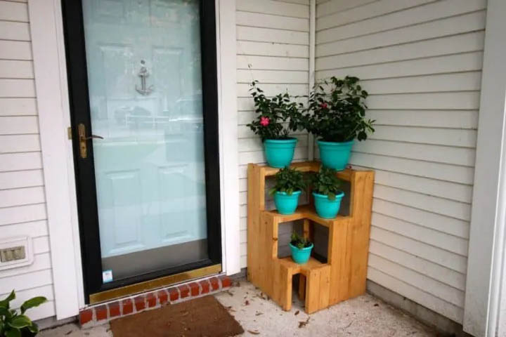 3 tiered plant stand with teal pots with plants in them
