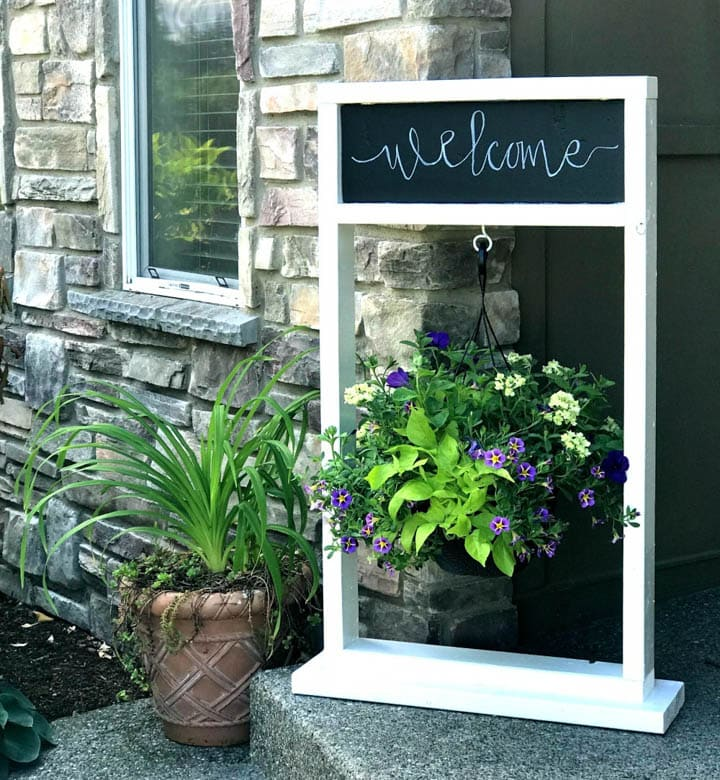 wooden DIY plant stand with hanging plant and chalkboard with welcome written on it