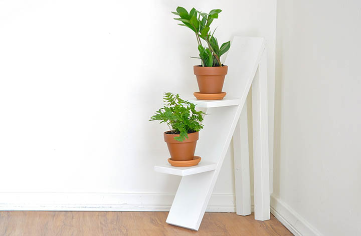 white two tiered plant stand with plants in clay pots
