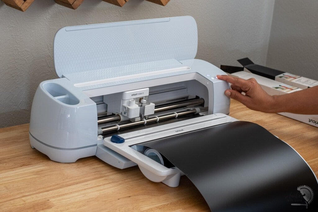 Woman running the Cricut Maker 3 with a black roll