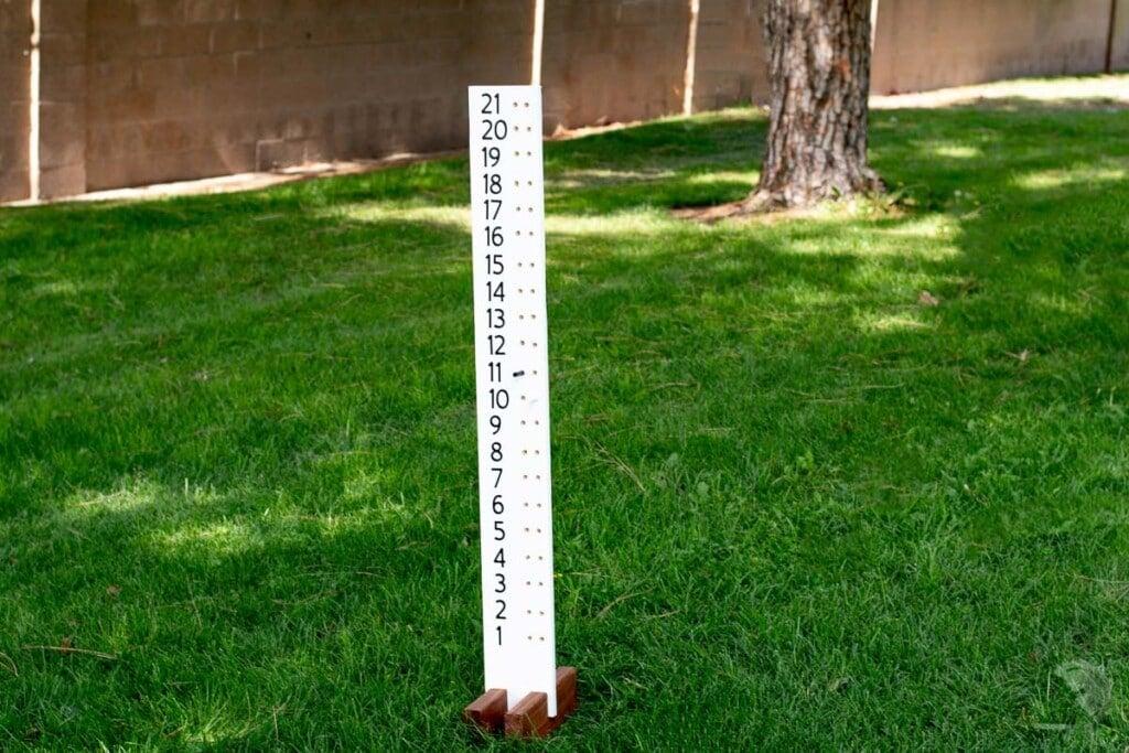 DIY cornhole board score keeper in grass.