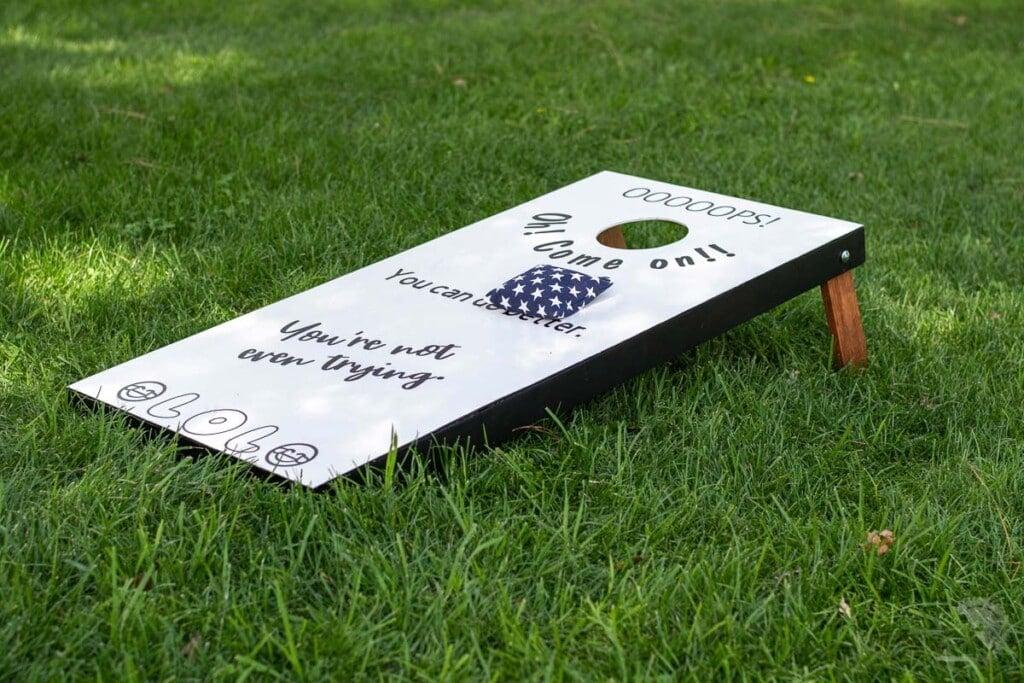 white cornhole board in the grass