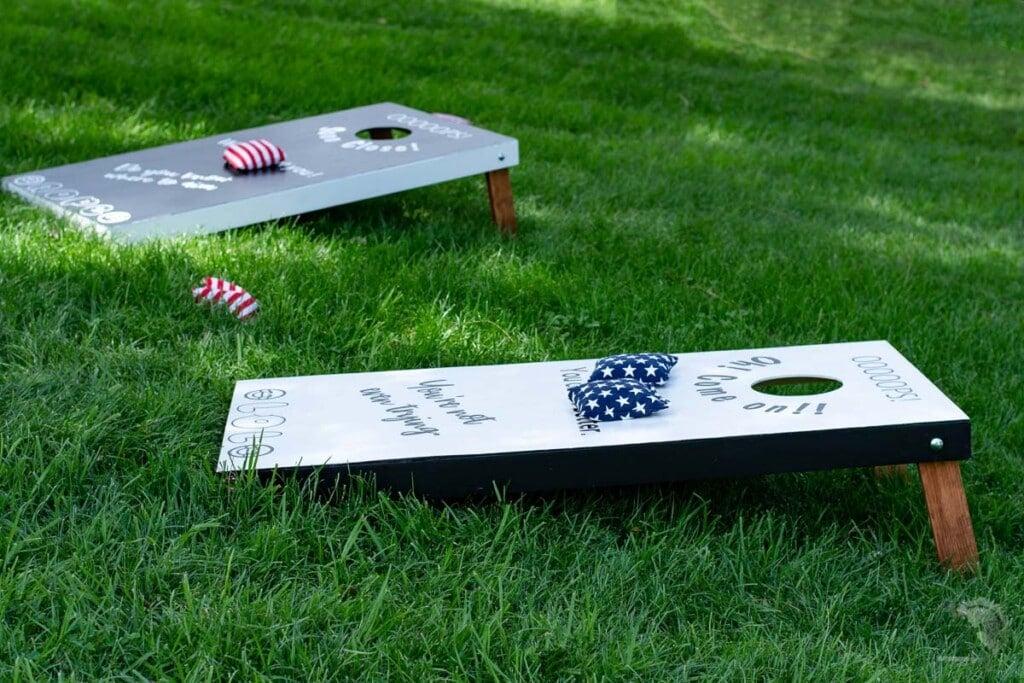 black and white cornhole boards in the grass