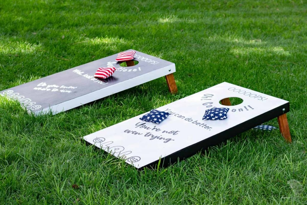 Black and while corn hole board in the grass