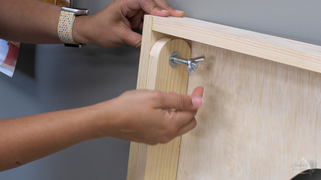 Woman attaching legs to cornhole board using carriage bolt and wing nuts