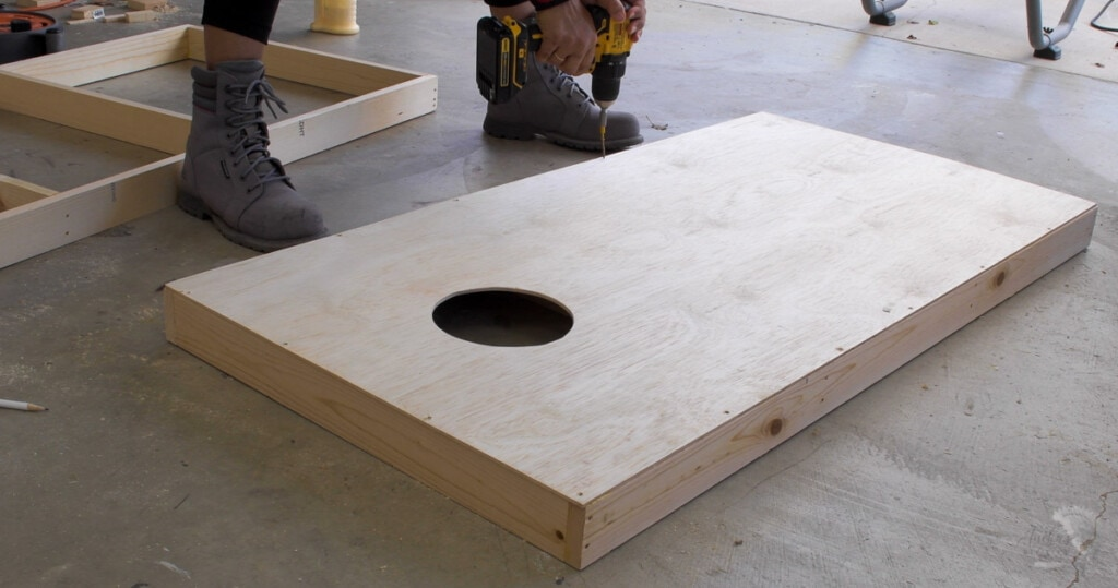 Woman attaching plywood to the frame to build the cornhole board