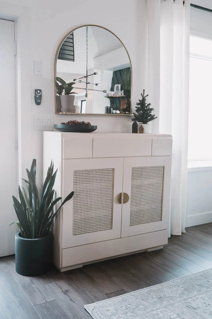 thrifted cabinet painted white with cane webbing door panels