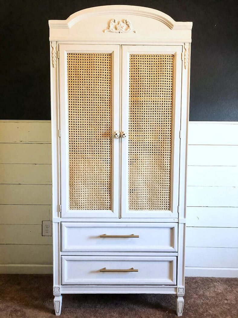 armoire painted white with cane webbing on the door panels.