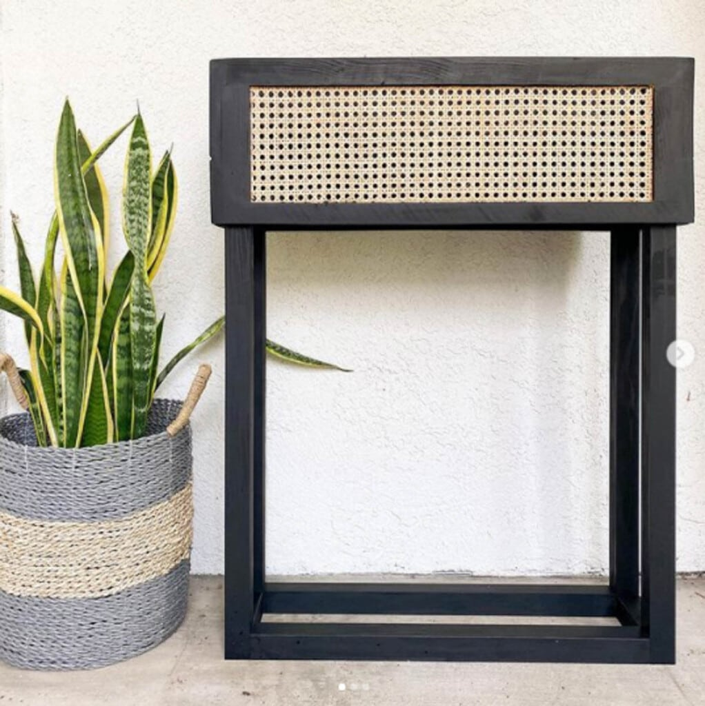 black painted wood plant stand with cane webbing