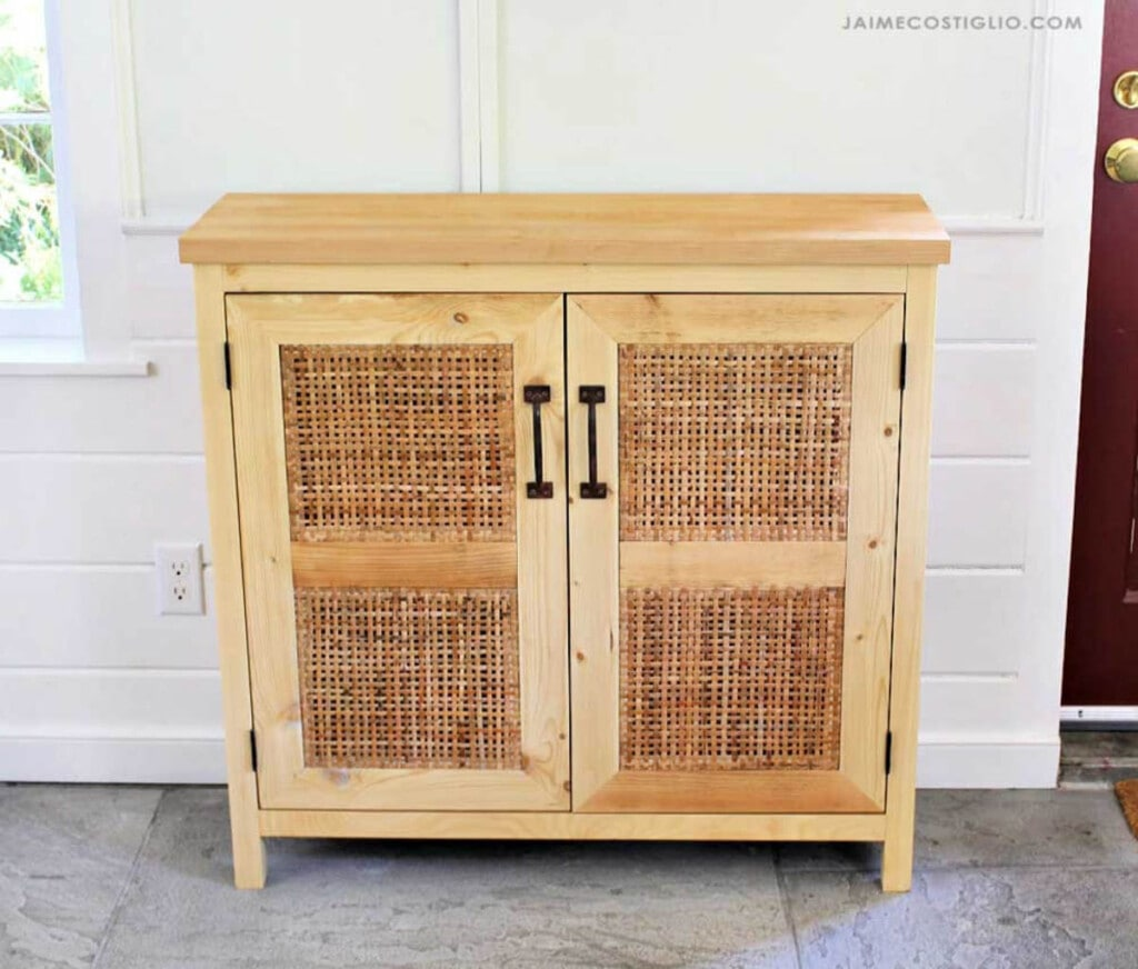 small wood console with two doors with cane webbing inserts